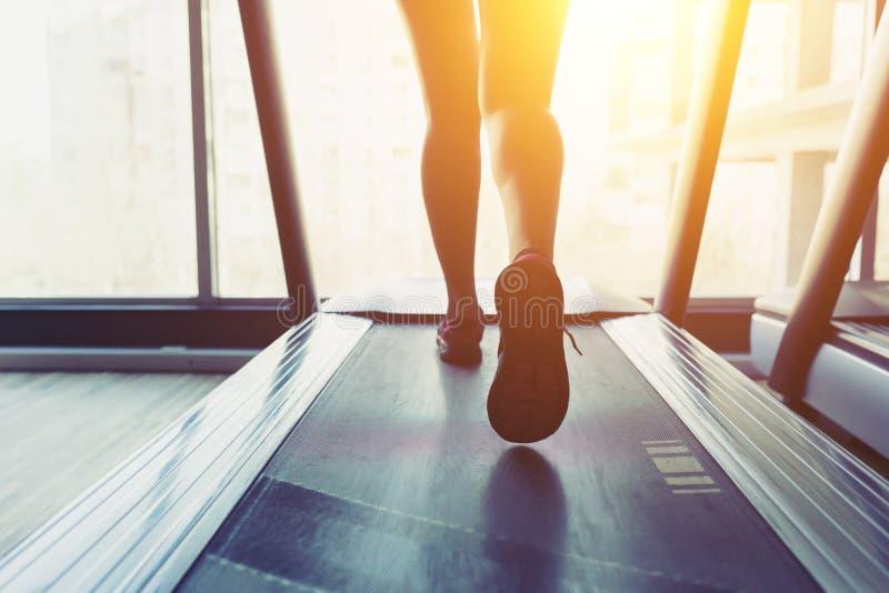 Девушка фитнеса бежать на третбане стоковая фотография