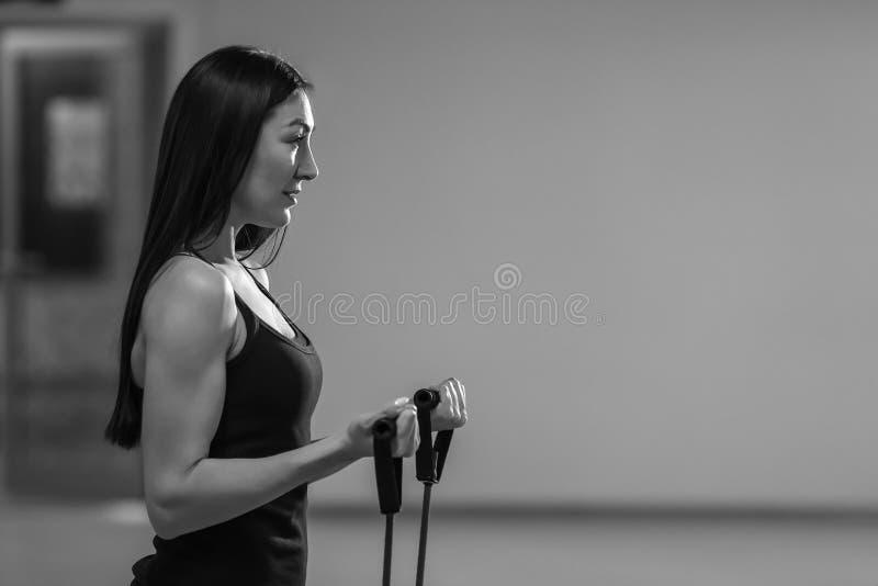 Девушка фитнеса выполняет тренировки с детандером Прочность и мотивировка стоковые фото