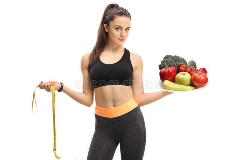 Девушка фитнеса держа измеряя ленту и плиту заполнила с fr стоковое фото rf