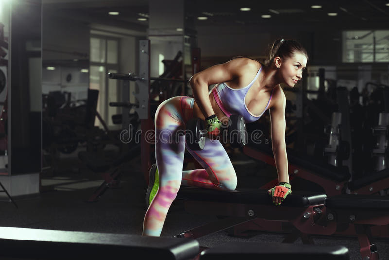 Девушка фитнеса молодая сексуальная в спортзале делая тренировки с гантелями стоковое изображение