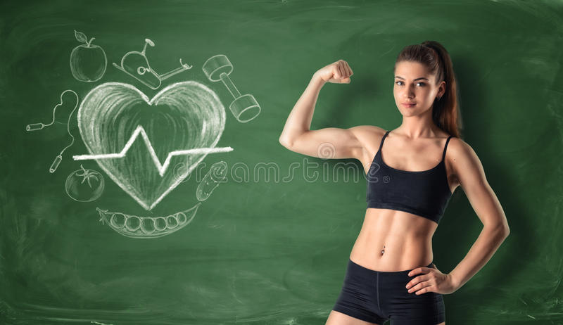 Девушка фитнеса показывая ее бицепс на предпосылке доски с вычерченными бить doodles сердца и спорта стоковые изображения rf
