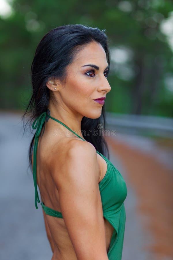 Девушка фитнеса представляя с красивым зеленым цветом swimsuit стоковые фото