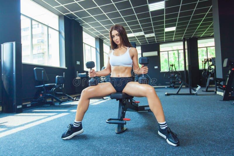 Девушка фитнеса привлекательной формы молодая sporty сфокусированная делая тренировки бицепса пока сидящ на тренируя приборе и стоковое изображение rf