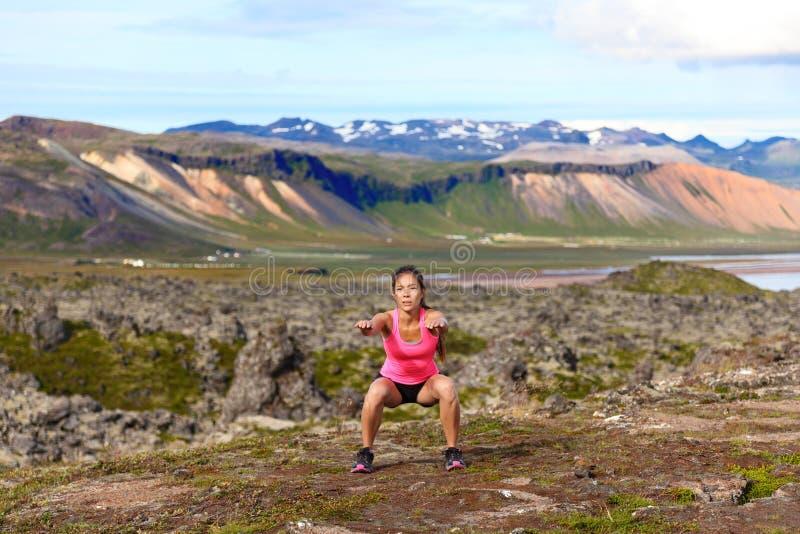 Девушка фитнеса работая outdoors делающ сидение на корточках скачки стоковое фото