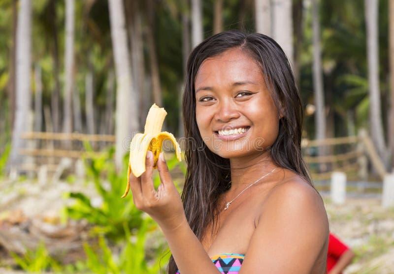 Девушка филиппинки есть банан стоковое фото