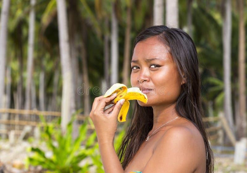 Девушка филиппинки есть банан стоковая фотография