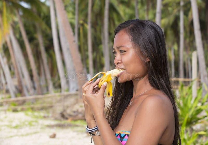 Девушка филиппинки есть банан Стоковое Изображение