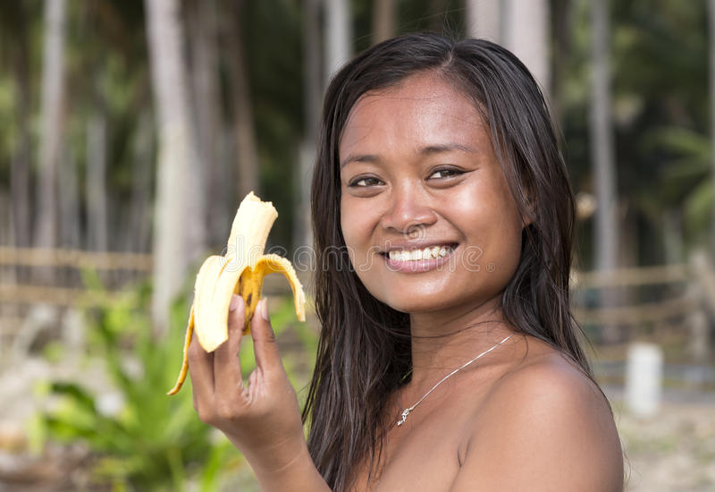 Девушка филиппинки есть банан стоковые фото