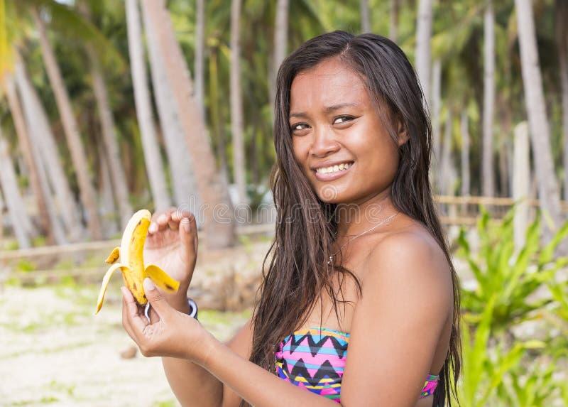 Девушка филиппинки есть банан стоковая фотография rf