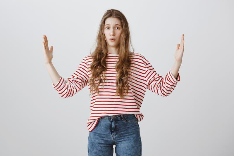 Девушка формируя огромный объект она невзлюбит Портрет confused и раздражанной молодой женщины показывая большую вещь с распростр стоковые изображения rf