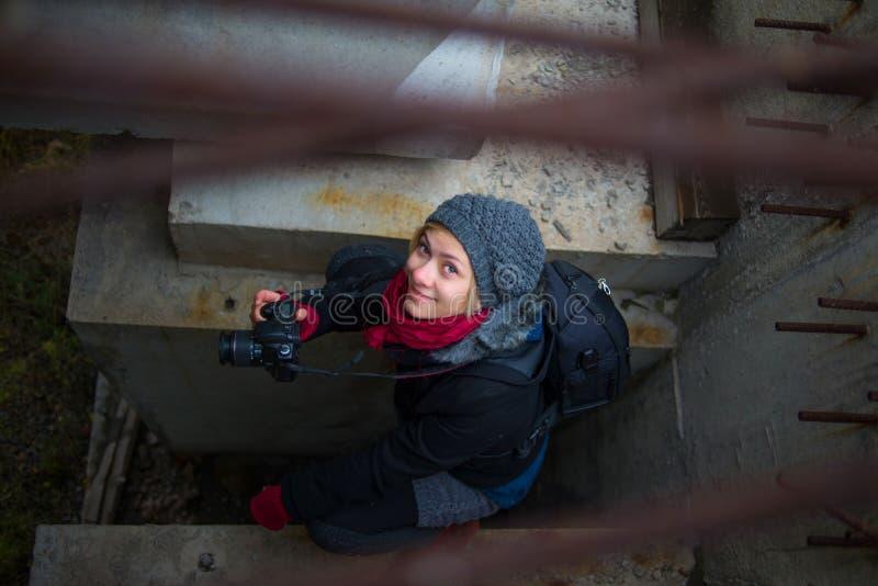 Девушка фотографа сидя на каменных слябах стоковые изображения