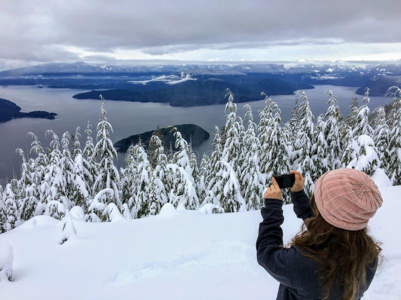 Девушка фотографируя на горе Cypress обозревая океан ниже стоковое фото