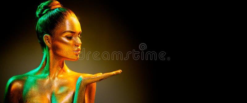 Девушка фотомодели в красочных ярких золотых sparkles показывая продукт на пустой руке пустой космос экземпляра стоковое изображение rf