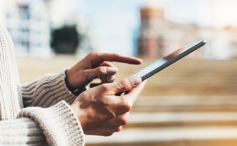 Девушка хипстера используя интернет технологии планшета, компьютер удерживания человека девушки на предпосылке Sun City, женской  стоковые фото