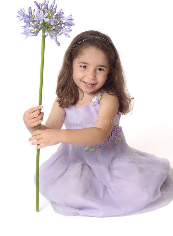 девушка цветка держа довольно усмехаться стоковая фотография