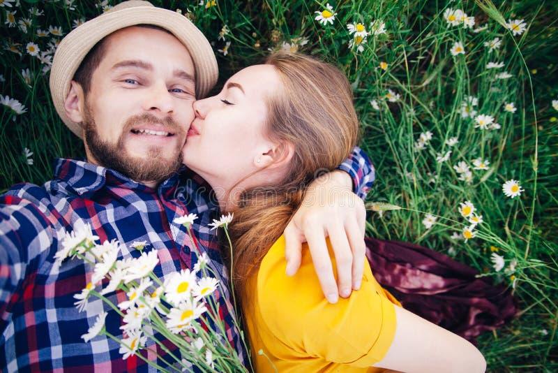 Девушка целует парня в поле стоковые изображения rf