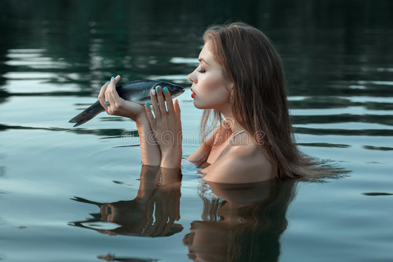 Девушка целует рыбу стоковое фото