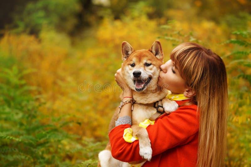 Девушка целует собаку Shiba Inu в парке осени стоковая фотография