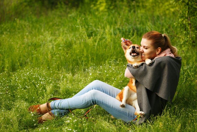 Девушка целуя собаку Shiba Inu стоковая фотография rf