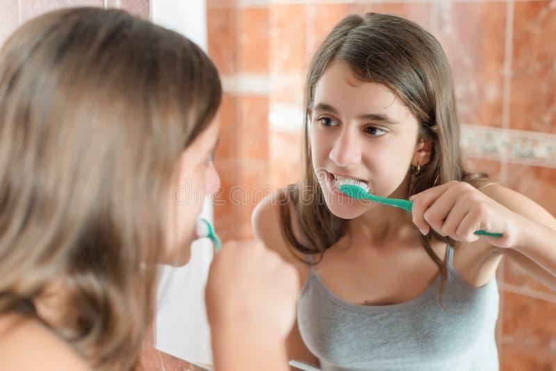 Девушка чистя ее зубы щеткой перед зеркалом стоковые изображения