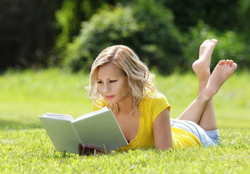 Девушка читая книгу. Белокурая красивая молодая женщина при книга лежа на траве. Внешний. Солнечный день стоковые изображения