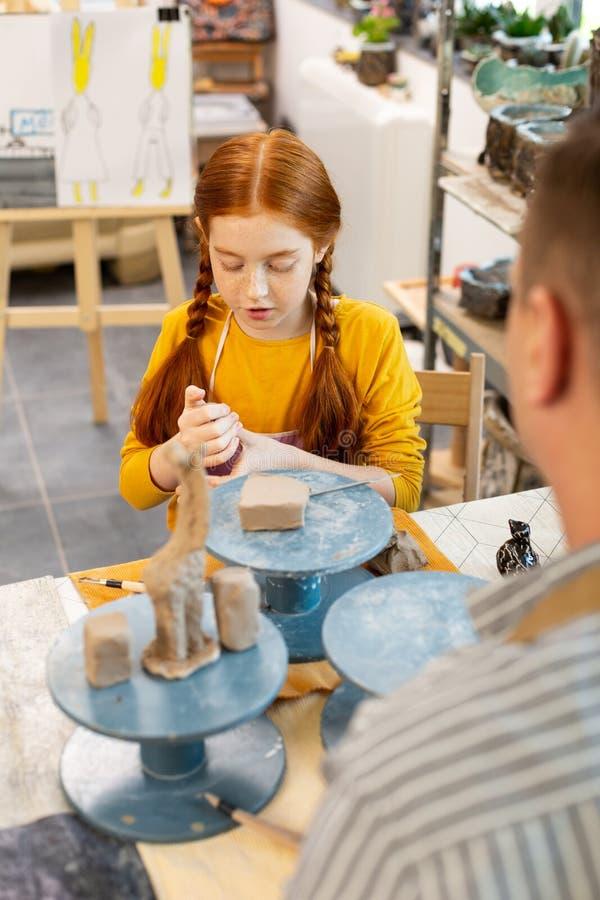 Девушка чувствуя любопытных моделируя животных с глиной в первый раз стоковое изображение rf