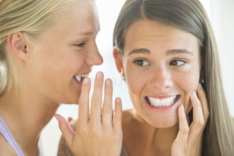 Девушка шепча в ухо друга стоковая фотография rf