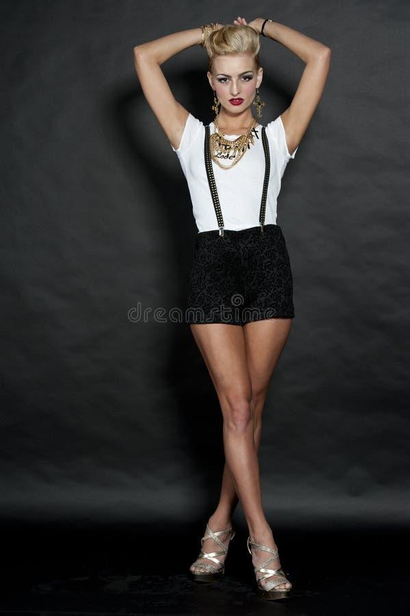 Девушка шикарной моды белокурая на черноте стоковое фото rf