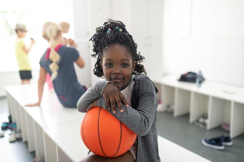 Девушка школы держа ее урок спорт баскетбола ждать стоковое фото