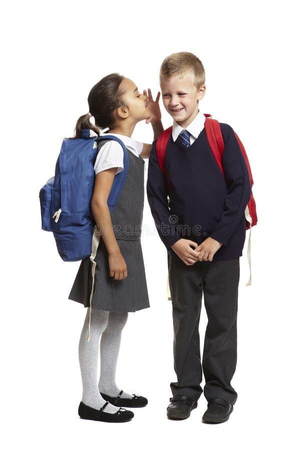 Девушка школы шепча в ухе мальчиков стоковое изображение