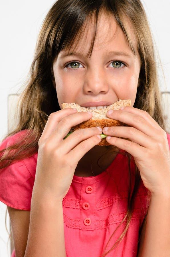 Девушка школы есть ее упакованный сандвич обеда стоковая фотография rf