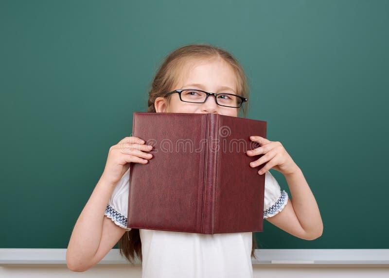 Девушка школы прочитала книгу, представляя на школьном правлении, пустой космос, концепция образования стоковая фотография rf