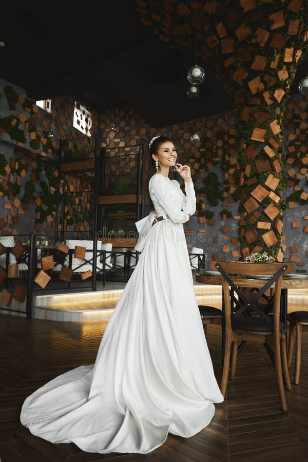 Девушка элегантного и красивого брюнета модельная с ярким макияжем и со стильным стилем причесок с ювелирными изделиями в белизне стоковые фото