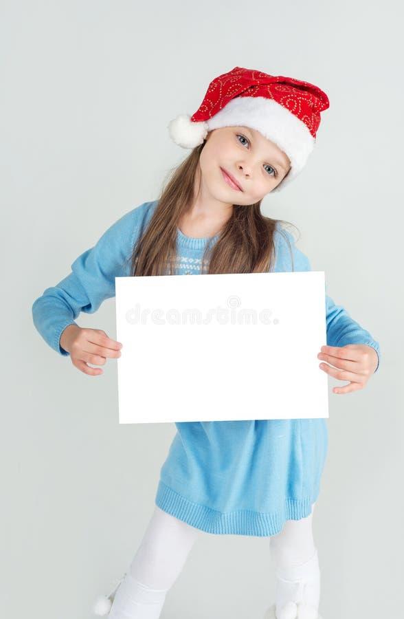 Девушка Юта ¡ Ð в шляпе Санта Клауса с белым листом чистого листа бумаги ¡ Ð стоковые фото