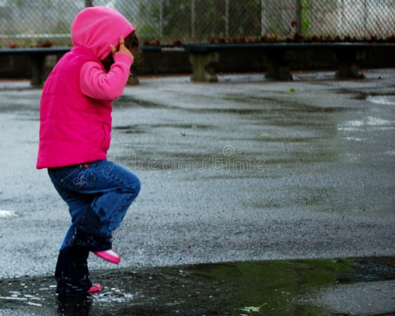 девушка 3 скача меньшяя лужица стоковое фото