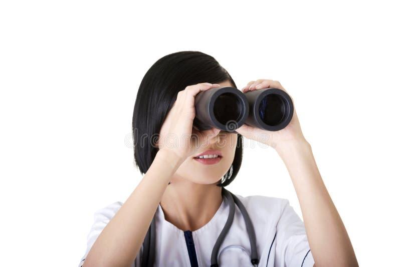 Девушка Atractive медицинская смотря через бинокли стоковое фото rf