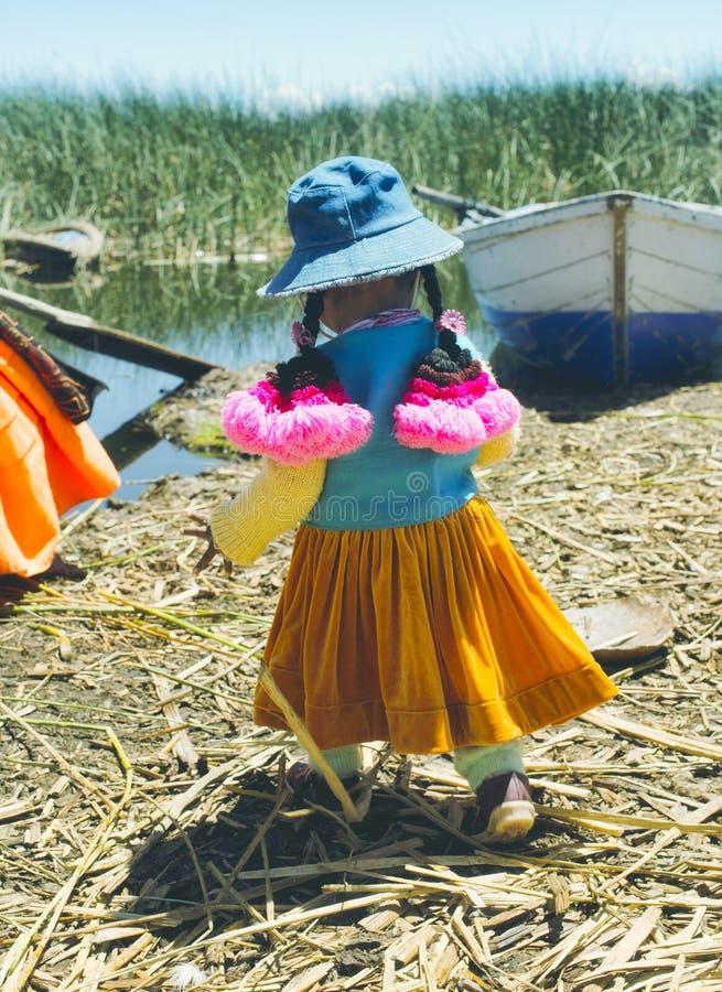 Девушка Aymara одела в обмундировании colorfull, островах Uros, Перу стоковые фотографии rf