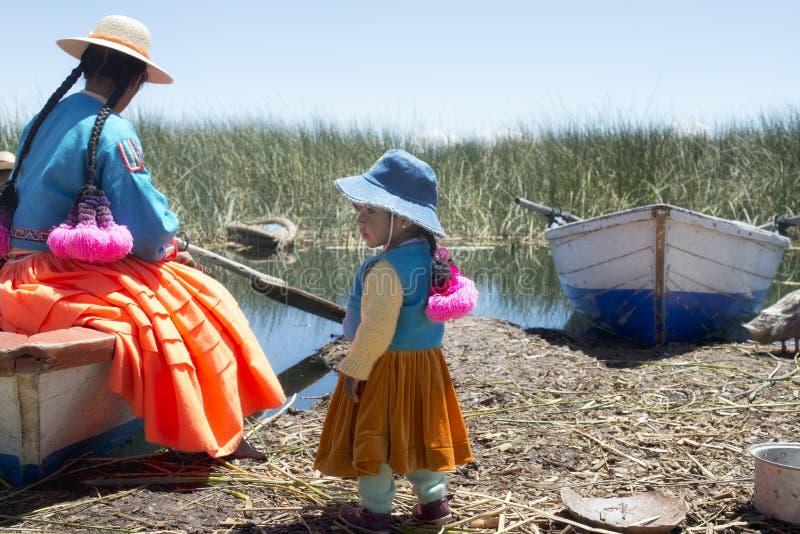 Девушка Aymara с ее матерью на shoreside на одном из островов Uros стоковая фотография