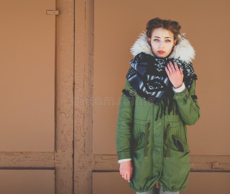 Девушка Bbeautiful необыкновенная в зеленой куртке рядом с коричневой дверью стоковое фото