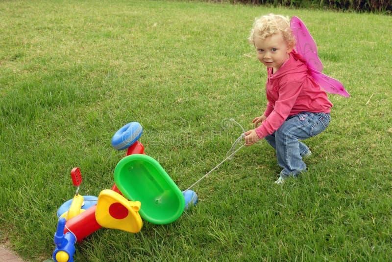 девушка blondie цветастая меньший играя трицикл стоковые фото