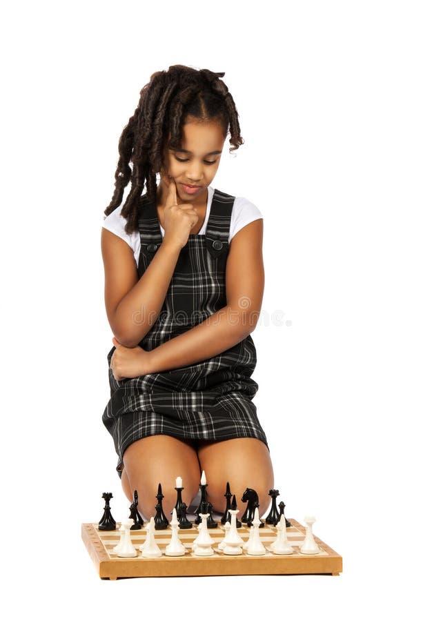 ДевушкаCleverиграя думать шахмат стоковая фотография