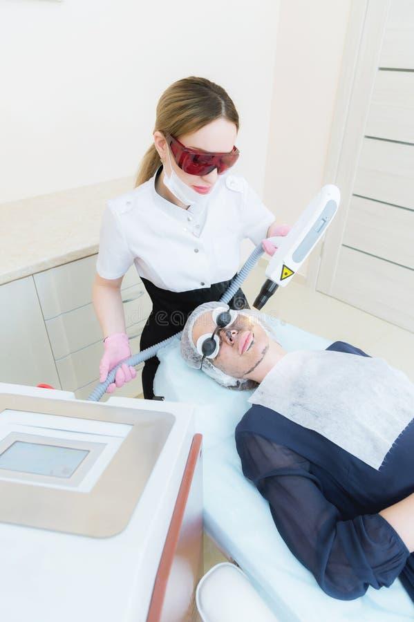 Девушка cosmetician в изумлённых взглядах делает процедуру шелушения углерода с помощью лазеру косметологии Сторона углерода стоковое изображение
