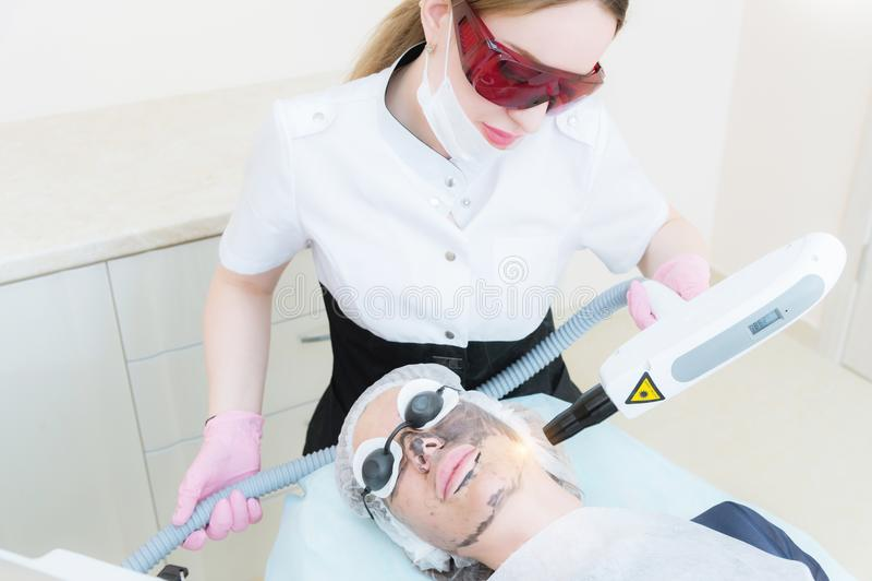 Девушка cosmetician в изумлённых взглядах делает процедуру шелушения углерода с помощью лазеру косметологии Сторона углерода стоковые фотографии rf