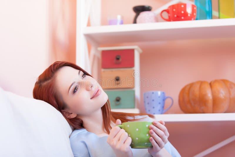 Девушка d в голубой блузке с зеленой чашкой стоковое фото rf