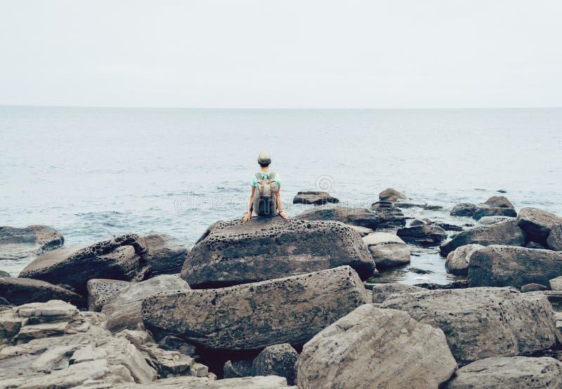 Девушка Hiker отдыхая на каменном побережье стоковые фотографии rf
