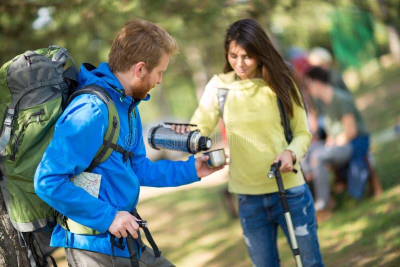 Девушка Hikers дает питье к ее мужскому другу стоковое фото