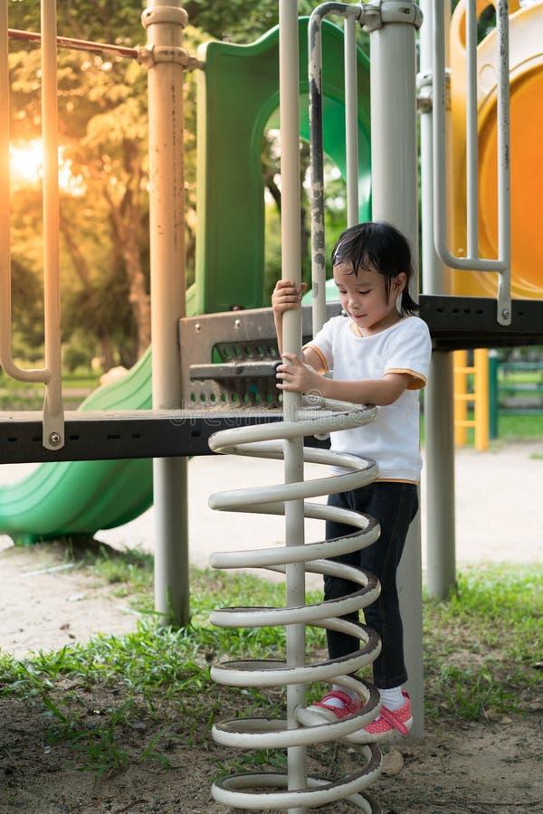Девушка Ittle взбирается вверх на лестнице формы весен стоковое изображение rf