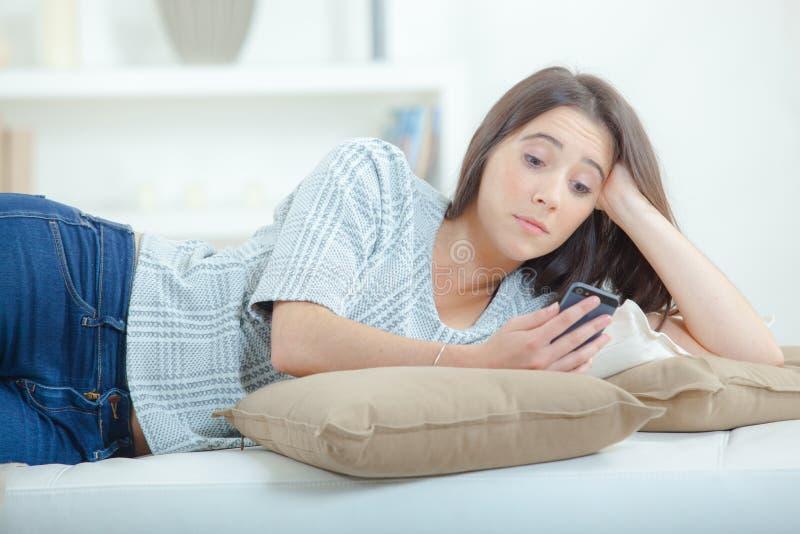 Девушка lounging с мобильным телефоном стоковое фото rf