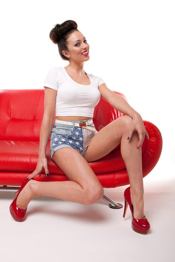 Девушка Pert Pinup на красной софе стоковые изображения