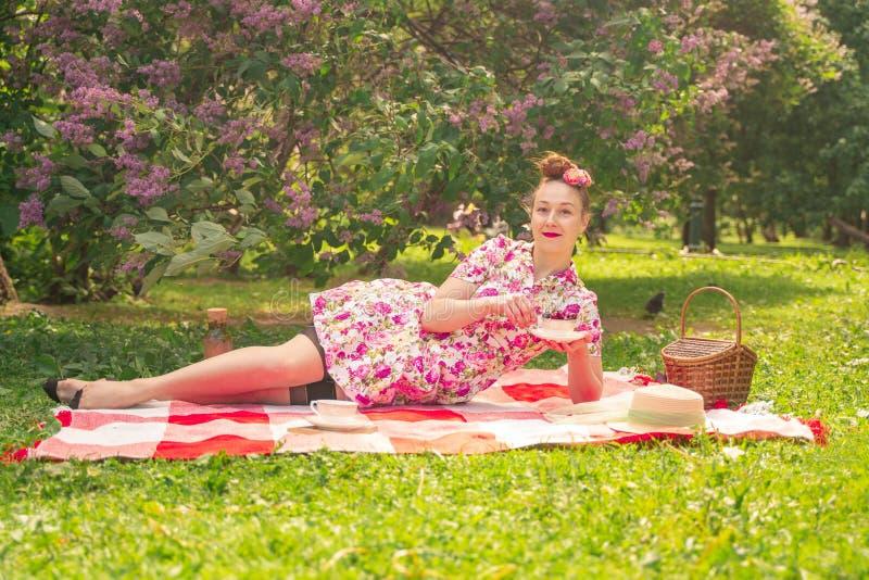 Девушка pinup возлюбленного очаровывая в платье лета на checkered одеяле в парке около кустов сирени наслаждается жизнью и leisu стоковые изображения